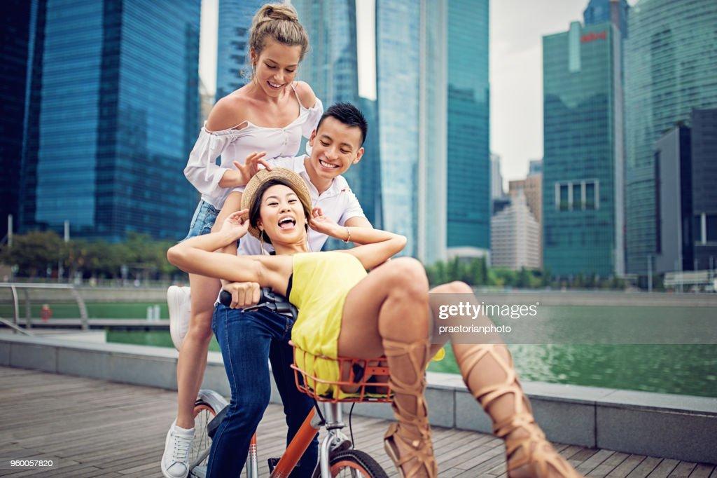 Glückliche Freunde reiten Fahrrad und machen Spaß zusammen : Stock-Foto