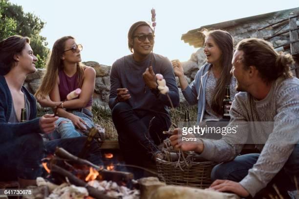 Glückliche Freunde Rösten Marshmallows am Strand