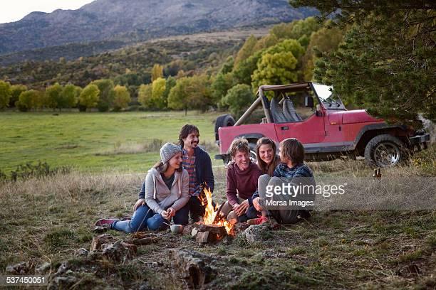 Happy friends sitting around campfire