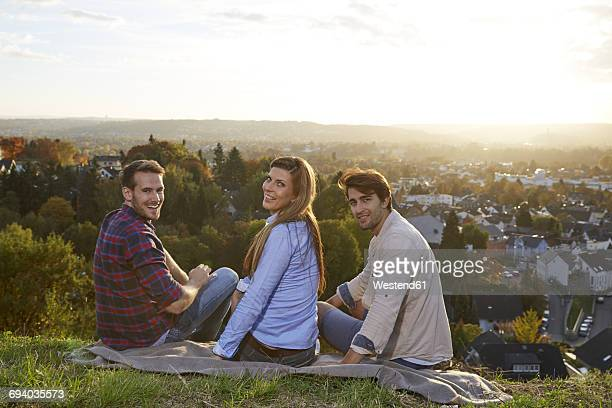 Happy friends sitting on a hill above a town
