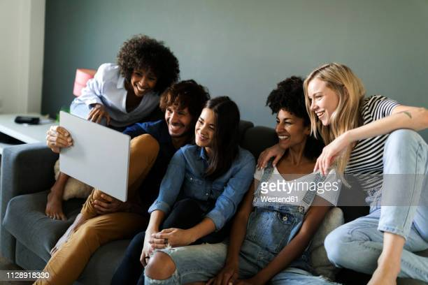 happy friends sitting on couch looking at tablet - stream stock pictures, royalty-free photos & images