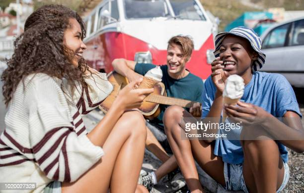 happy friends sitting on curb with guitar and soft ice cream - alternative lifestyle stock pictures, royalty-free photos & images