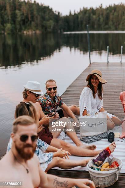 happy friends sitting on jetty - sweden stock pictures, royalty-free photos & images
