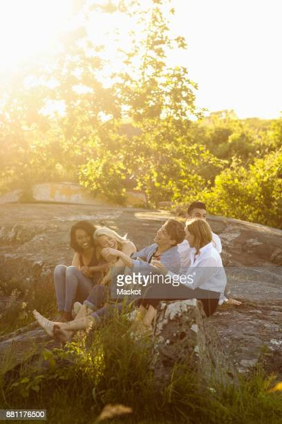 Happy friends sitting on rock formation against trees during sunny day