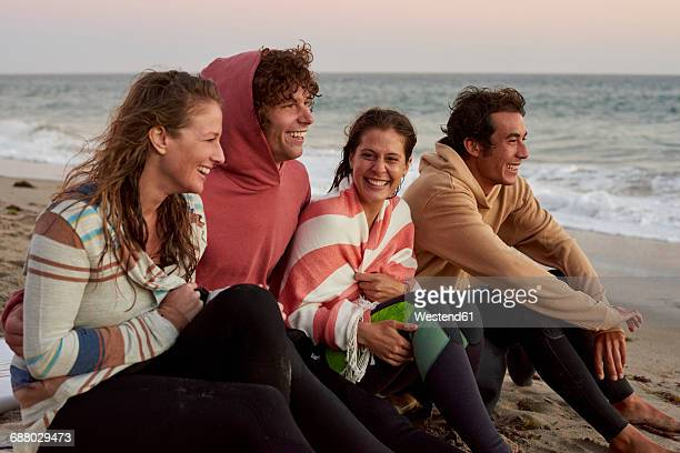Happy friends sitting on the beach in the evening