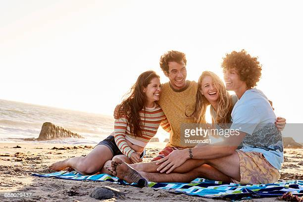 happy friends sitting on the beach - four people stock pictures, royalty-free photos & images