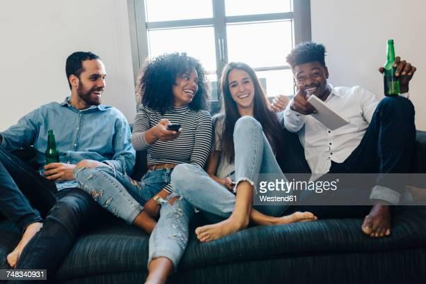 happy friends sitting on the sofa watching tv - quattro persone foto e immagini stock
