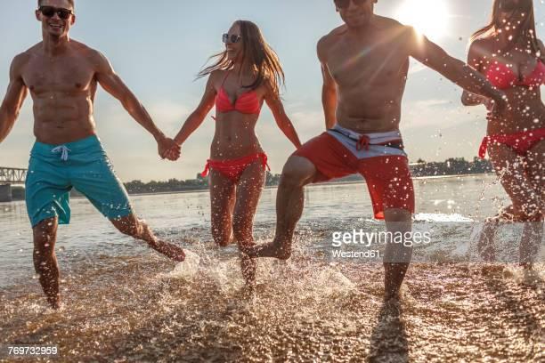 Happy friends splashing in water