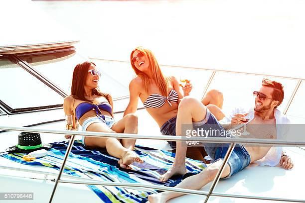 Happy friends sunbathing on yacht.