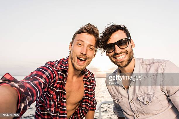 Happy friends taking a selfie on boat.