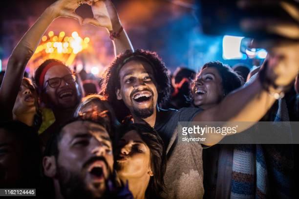 amigos felizes que tomam um selfie no festival de música em a noite. - performance - fotografias e filmes do acervo