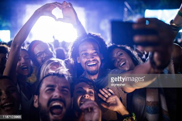 happy friends taking a selfie on music festival by night. - popular music concert stock pictures, royalty-free photos & images