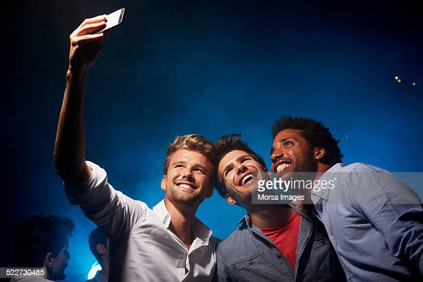 Happy friends taking self portrait at nightclub
