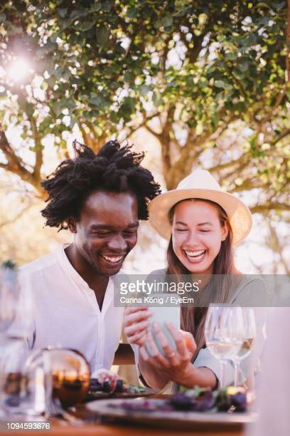 happy friends taking selfie while having lunch in park - photo messaging stock pictures, royalty-free photos & images