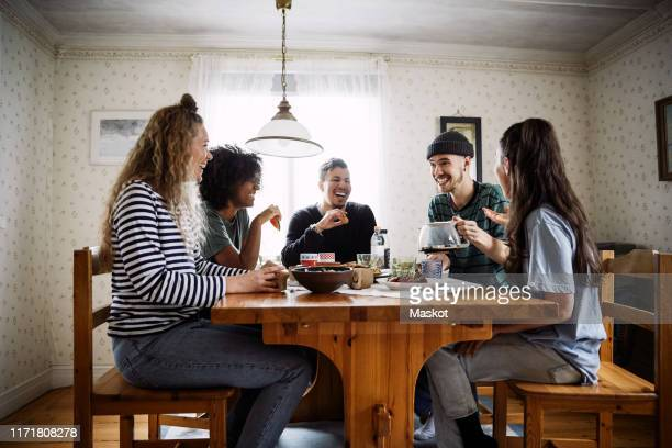 happy friends talking while enjoying food and drink on table at home - five people stock pictures, royalty-free photos & images