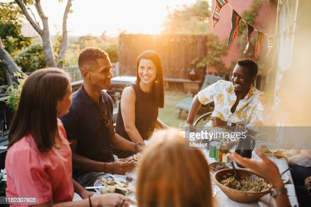 happy friends talking while enjoying food in dinner party - invité photos et images de collection
