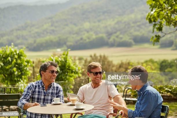 Amigos felizes hablando y merendando en el patio