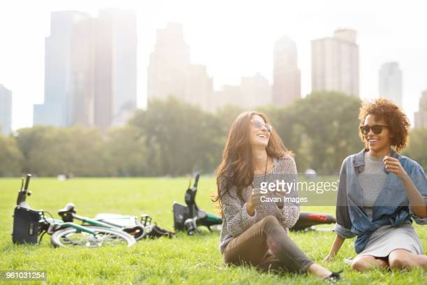 happy friends talking while sitting on grassy field - ensolarado imagens e fotografias de stock