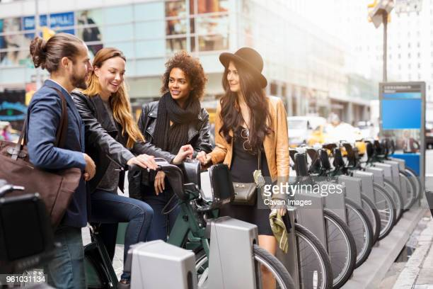 happy friends talking while standing at parking lot in city - bicycle parking station stock photos and pictures