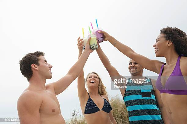Happy Friends Toasting Boba Milk Against Clear Sky