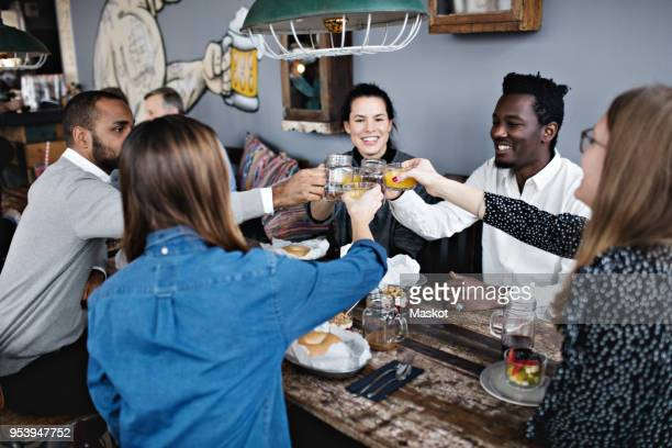 Happy friends toasting drink while sitting at dining table in restaurant