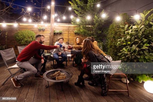 happy friends toasting drinks in party at night - fire pit stock pictures, royalty-free photos & images
