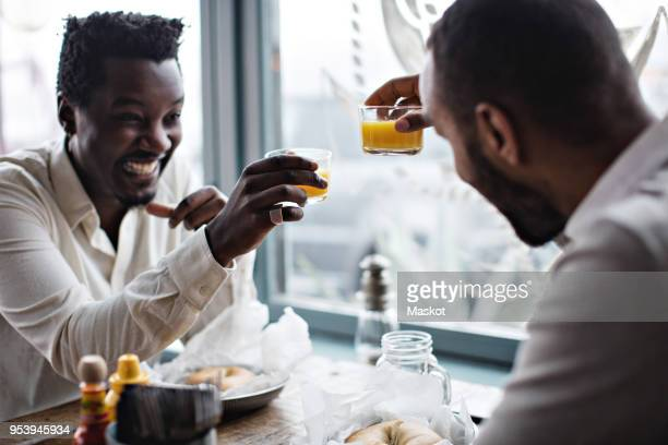 happy friends toasting drinks while sitting at table in restaurant - the brunch stock pictures, royalty-free photos & images