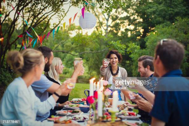 Happy friends toasting glasses at table in garden party