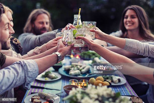 happy friends toasting mojito glasses at dinner table in yard - cocktail party stock pictures, royalty-free photos & images