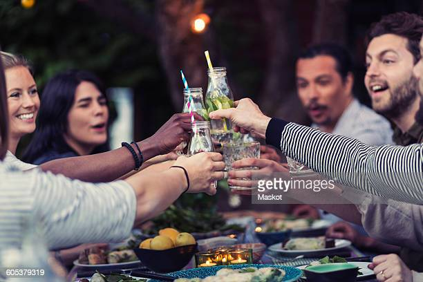 Happy friends toasting mojito glasses at table during dinner party in yard