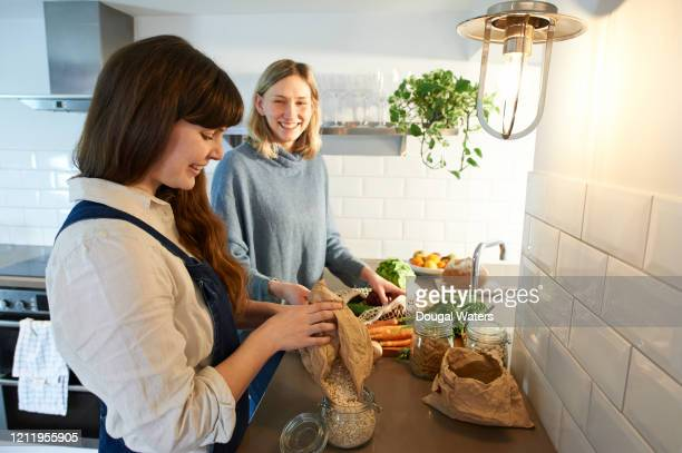 happy friends unpacking shopping from plastic free bag. - sustainable lifestyle stock pictures, royalty-free photos & images