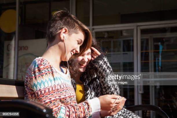 happy friends using mobile phone while sitting on bench - half shaved hairstyle stock pictures, royalty-free photos & images