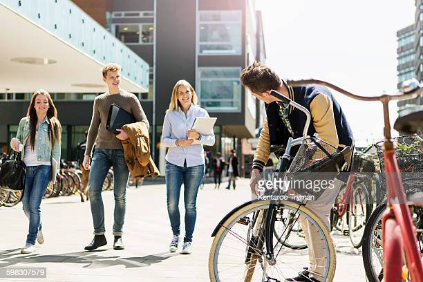 Happy friends walking by man with bicycle at campus