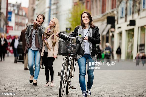 Happy friends walking in the city with a bycicle