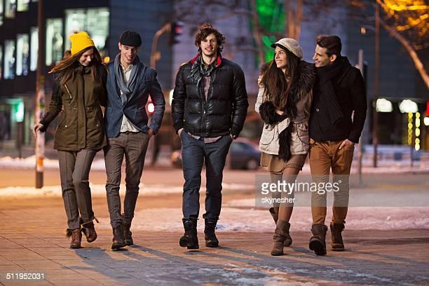 Happy friends walking in the street.