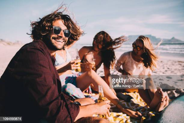 happy friends with alcoholic drinks sitting at beach against sky during sunny day - men friends beer outside stock pictures, royalty-free photos & images