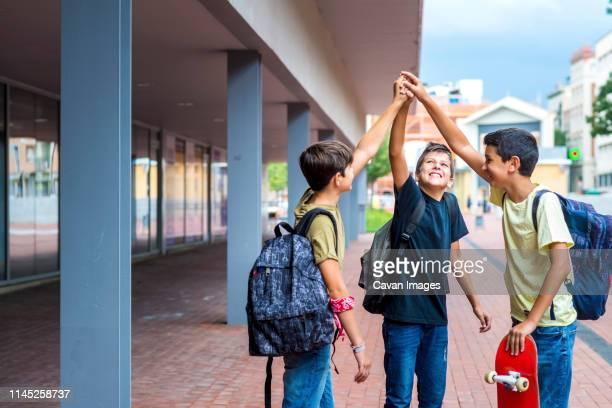 happy friends with arms raised standing on footpath against buildings - preadolescente fotografías e imágenes de stock