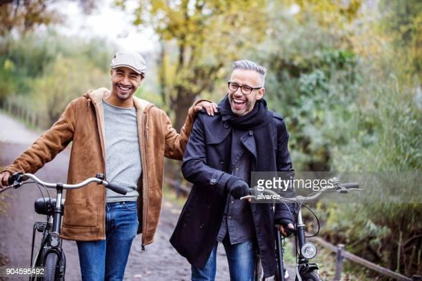 Glückliche Freunde mit dem Fahrrad, zu Fuß durch Pflanzen