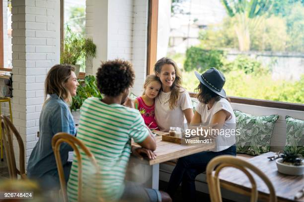 Happy friends with child socializing in cozy cafe
