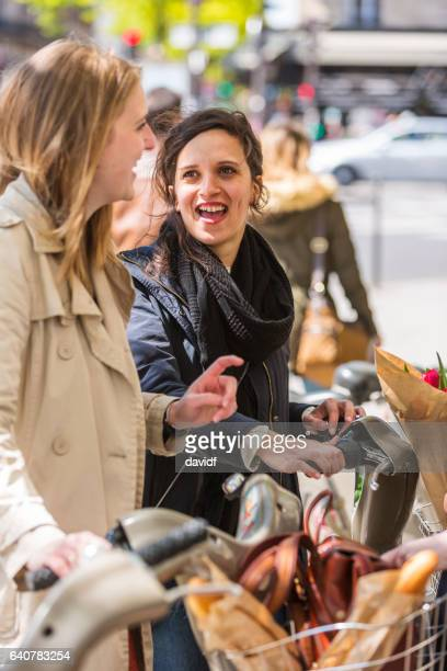 happy friends with hire bicycles in paris - french women stock photos and pictures