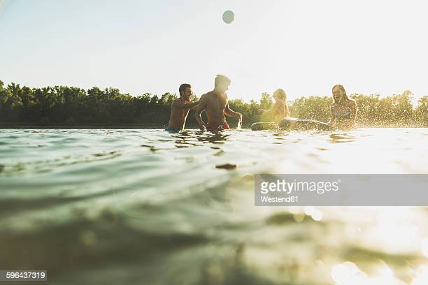 happy friends with inner tubes and ball in water - taking a bath stock pictures, royalty-free photos & images