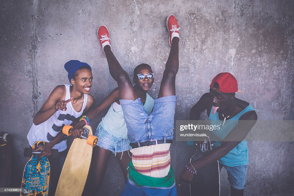 Happy friends with longboards having fun with crazy poses : Stock Photo