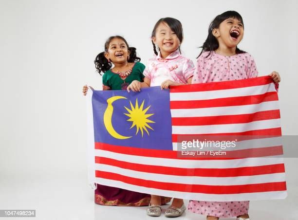 happy friends with malaysian flag against white background - malaysian culture stock pictures, royalty-free photos & images