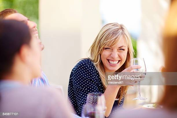 Happy friends with red wine glasses outdoors