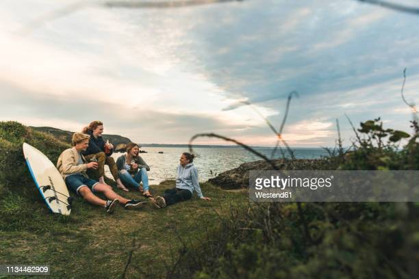 happy friends with surfboard and drinks socializing at the coast at sunset - finistere stock photos and pictures