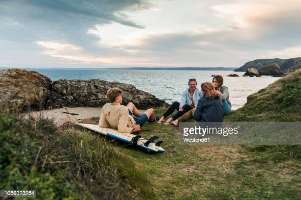 happy friends with surfboard socializing at the coast at sunset - finistere stock photos and pictures