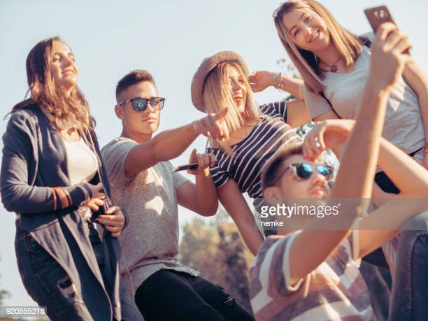 Happy friendship concept with young people having fun together taking selfie
