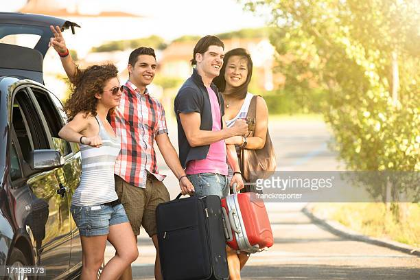 Happy friendship ready for a vacation with car