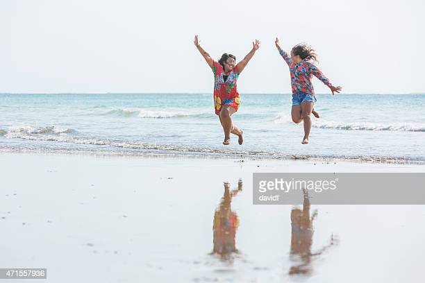 happy full figured asian women running on the beach - chubby asian woman stock pictures, royalty-free photos & images