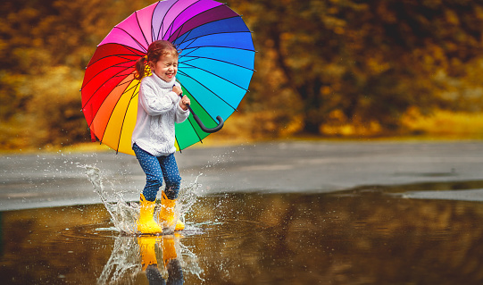 Happy funny child girl with  umbrella jumping on puddles in rubber boots 836684354